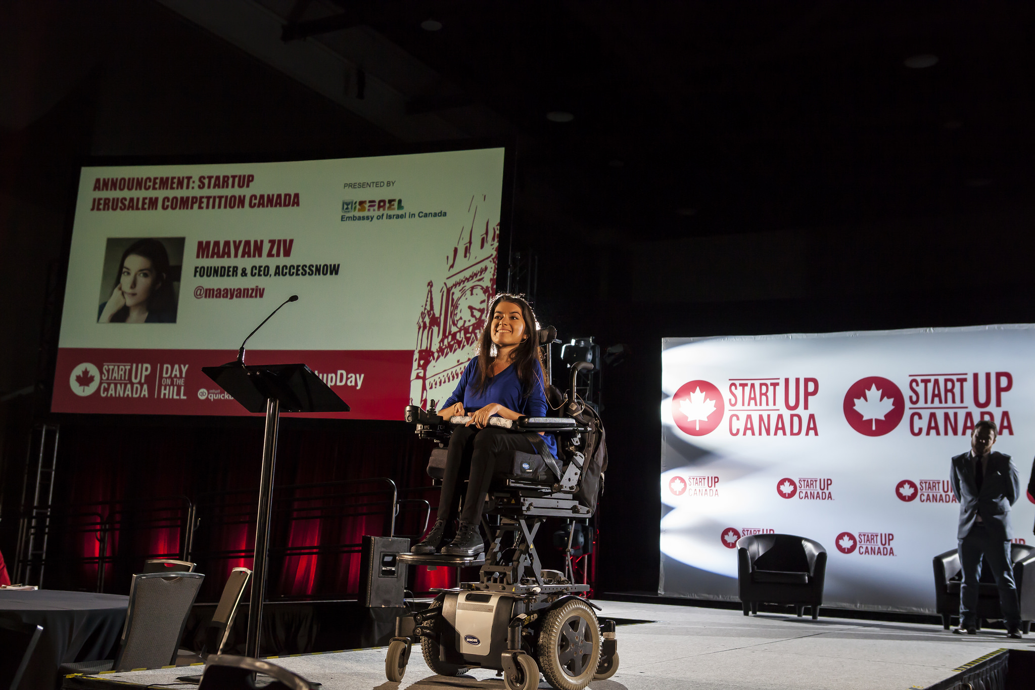 """maayan smiles on stage at the startup canada day on the hill event. behind her is a large screen that reads """"Announcement: Startup Jerusalem Competition Canada"""" in red"""