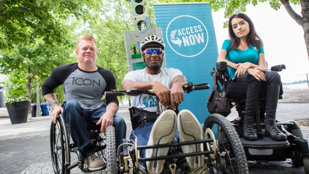 Jeff adams, left, anthony lue, centre, maayan ziv right, pose with accessnow banner. all pictured are wheelchair users.