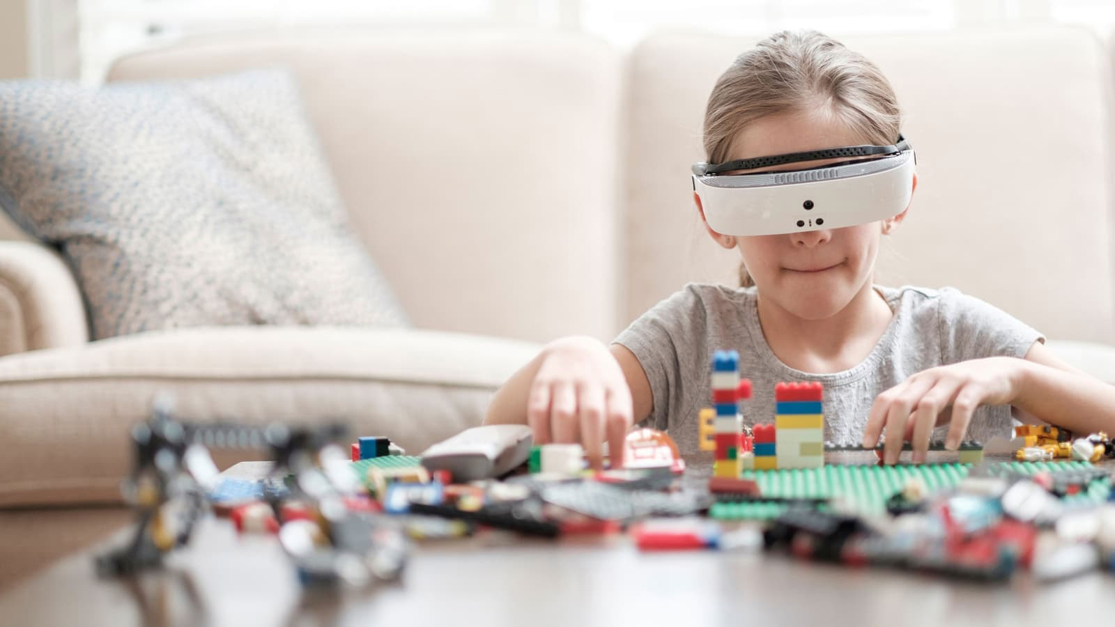 young girl plays with legos while wearing esight visor