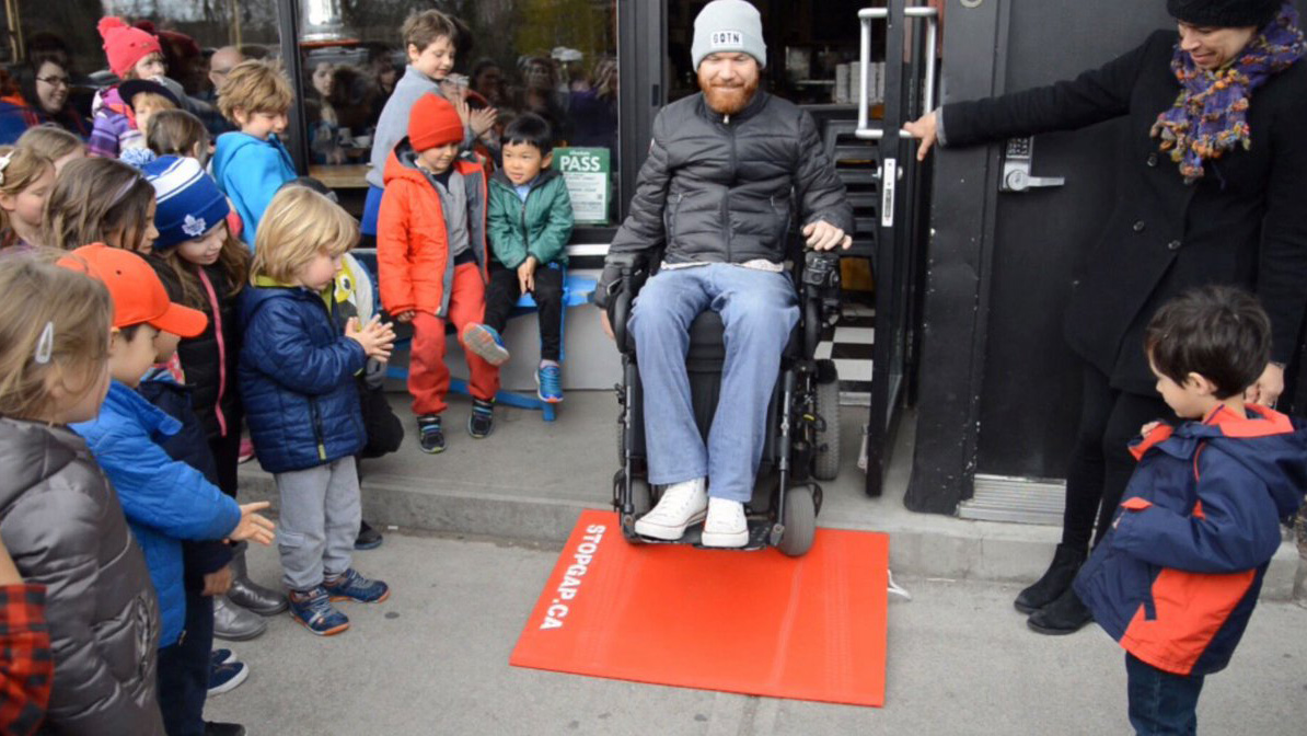 luke anderson drives his wheelchair down a stopgap ramp while children look on
