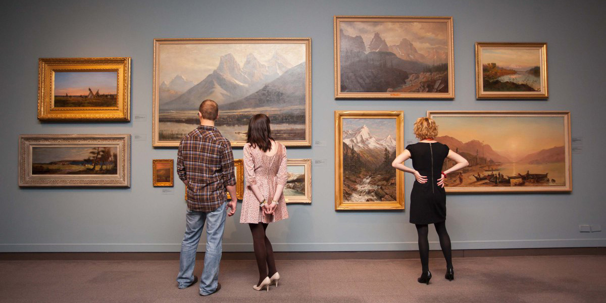 three people stand looking at a wall of landscape paintings in a museum
