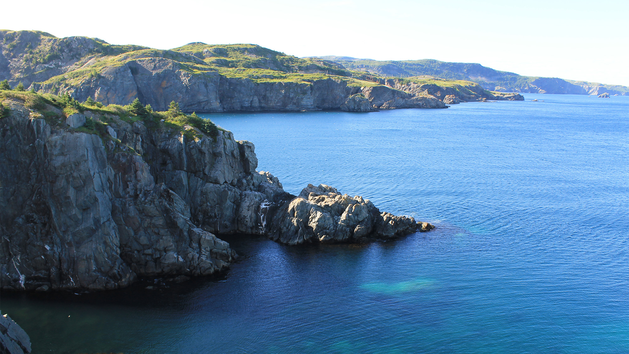 birds eye view of clear blue waters and jagged rocks