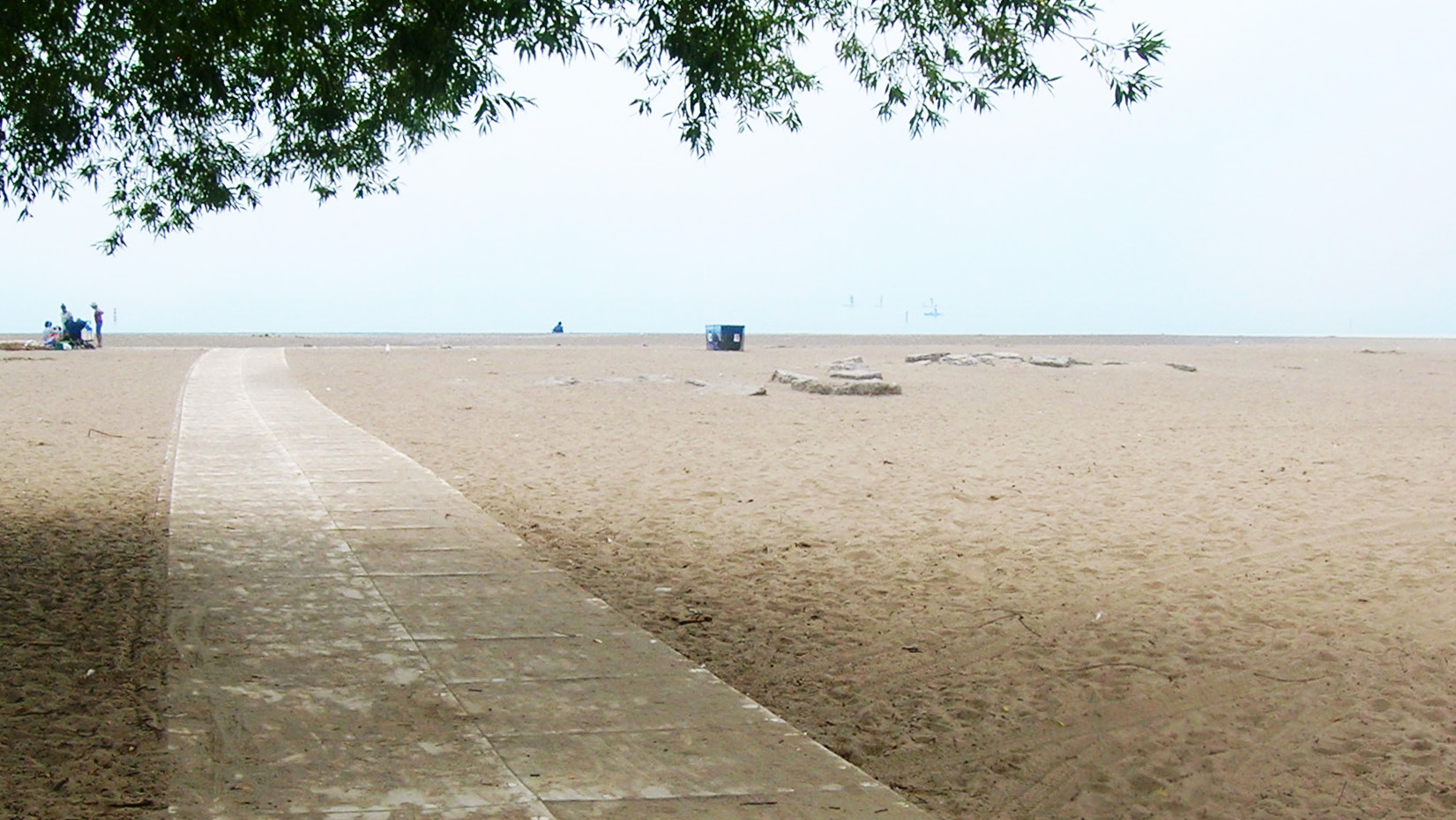 mesh pathway extends over sand towards the water