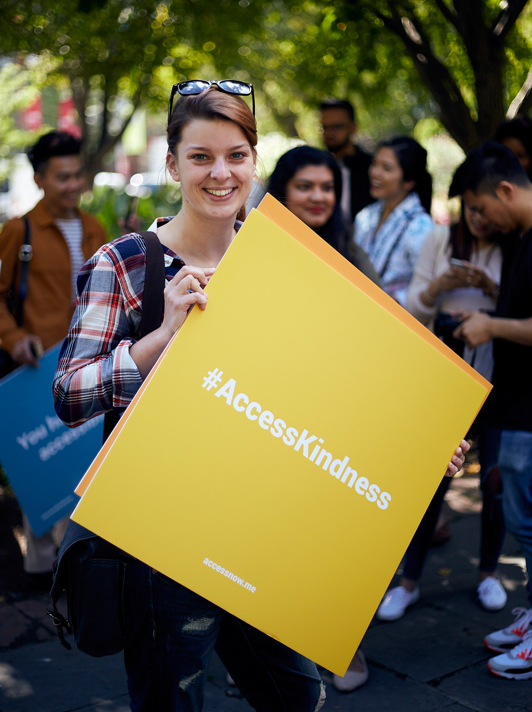 """photo of young woman smiling as she holds up a yellow sign that reads """"Access Kindness"""" in bold"""